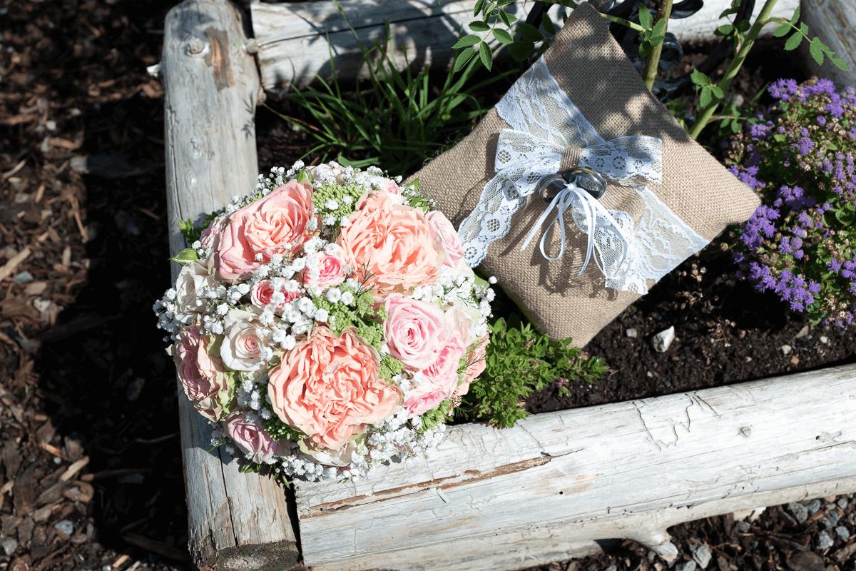 Brautstrau und Eheringe auf Kissen