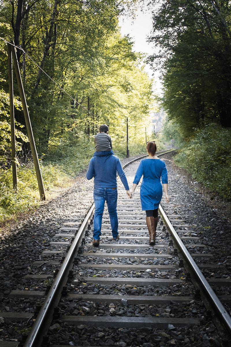 Familie spaziert Bahngleise entlang