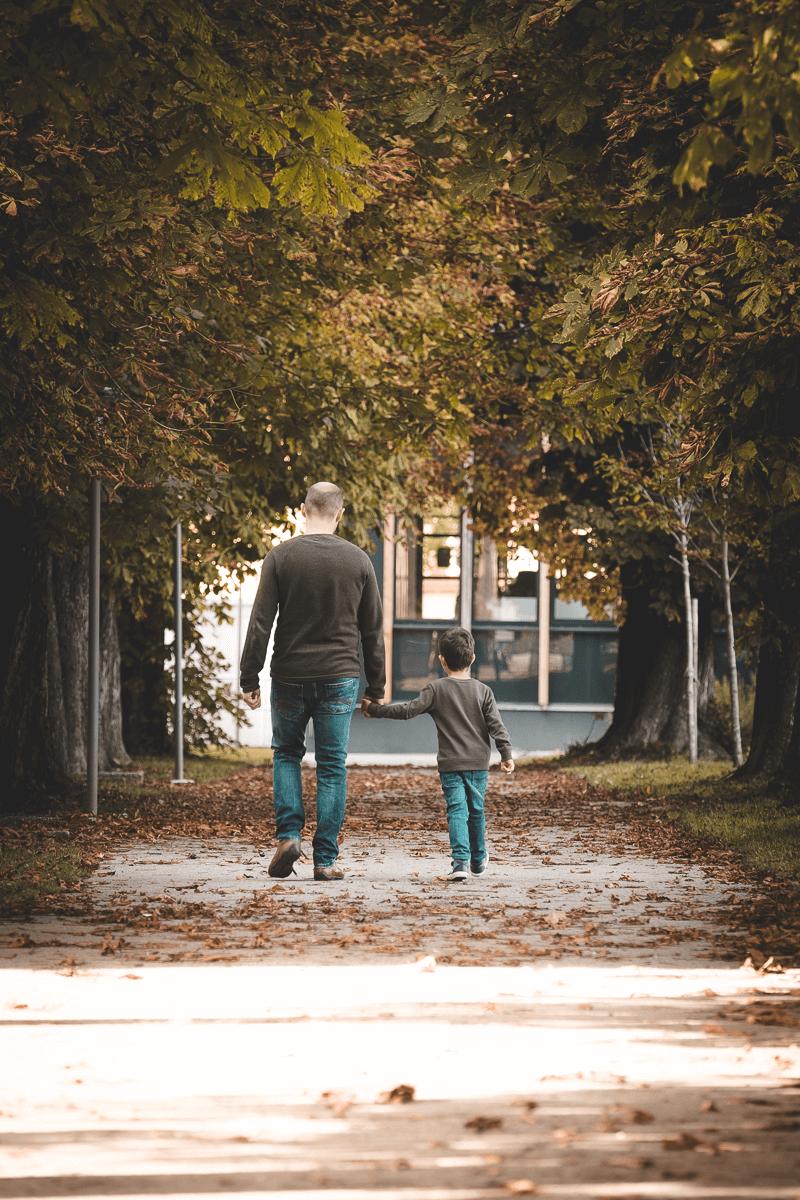 Vater geht Hand in Hand mit Sohn spazieren