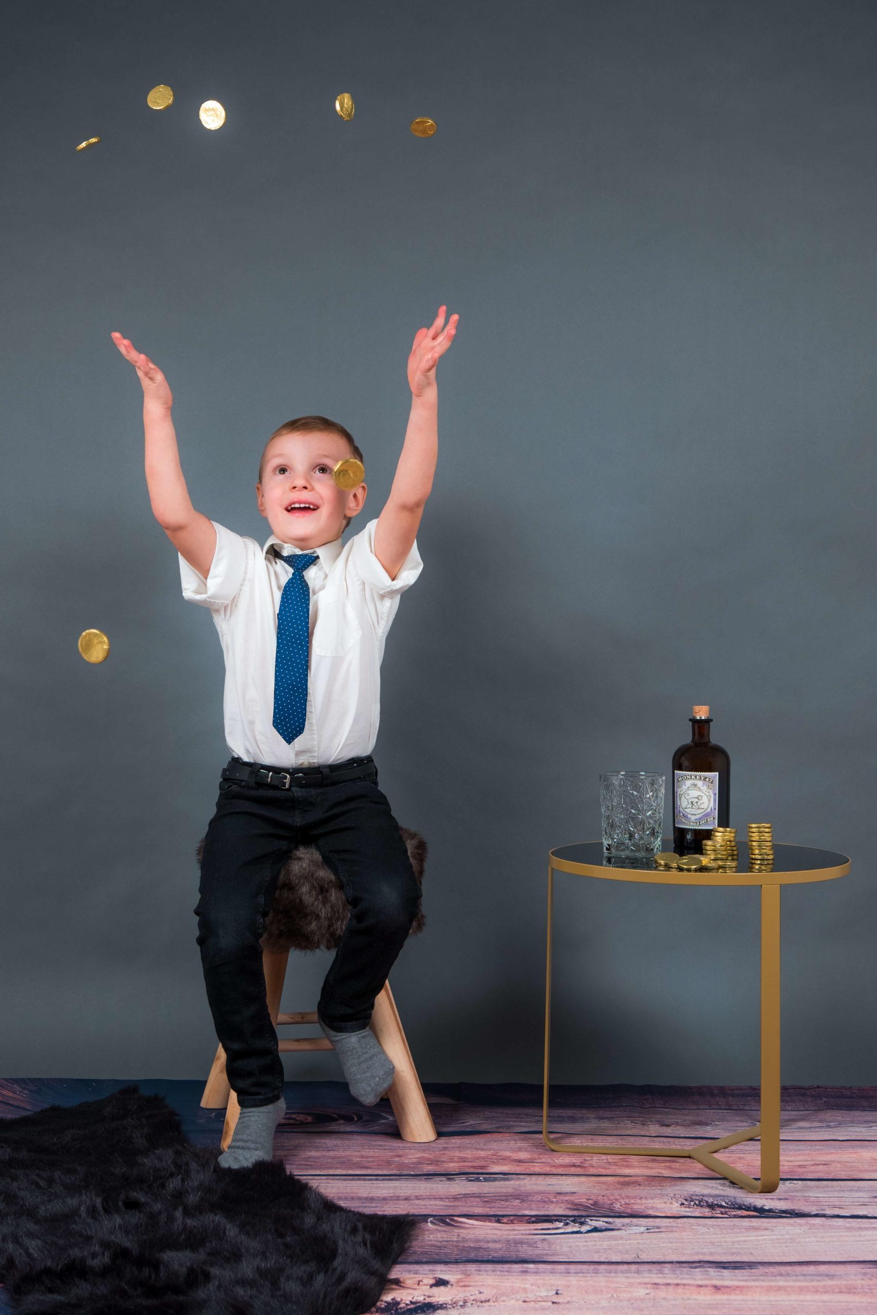 Junge spielt mit Goldmünzen