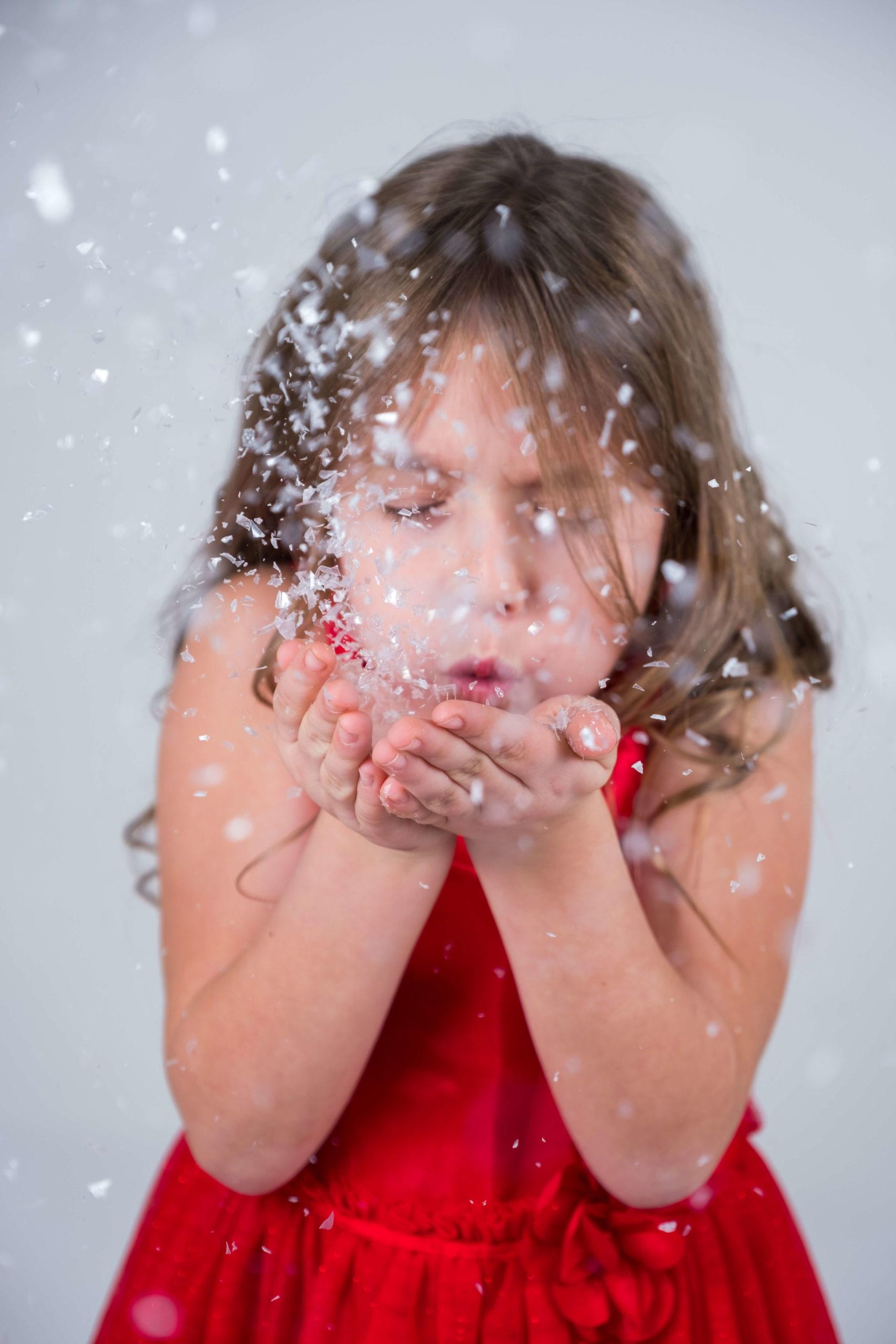 Mädchen pustet Schnee weg