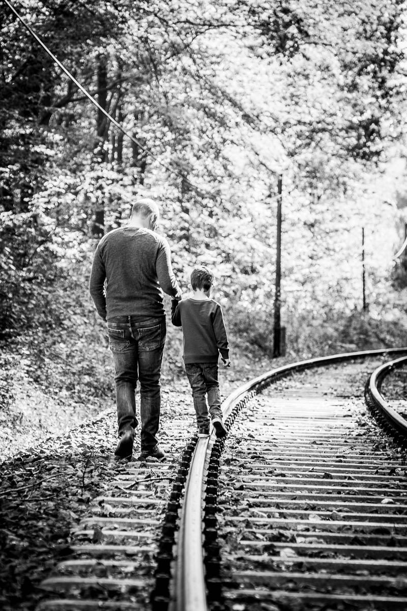 Vater balanciert mit Sohn auf Bahngleis