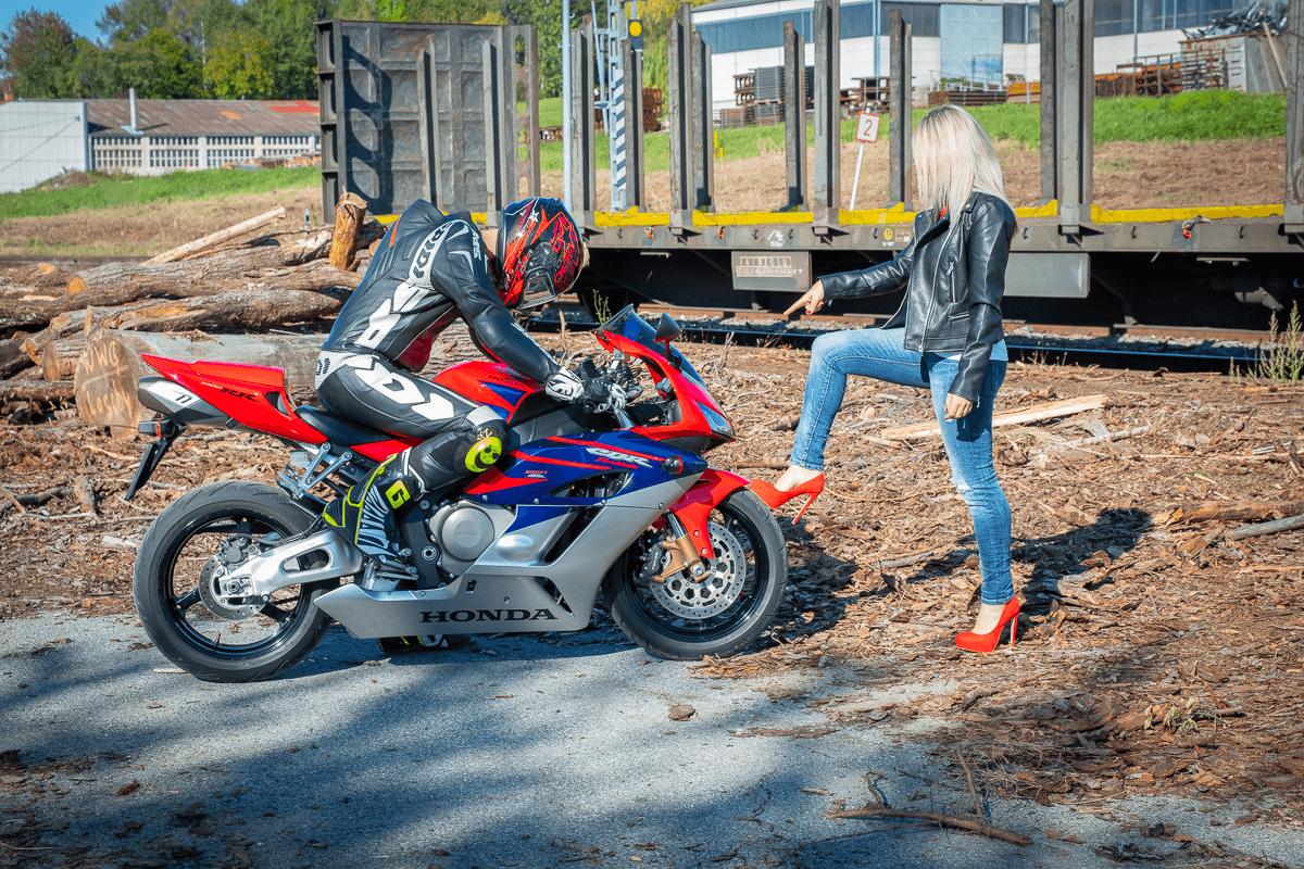 Frau steht vor Motorradfahrer